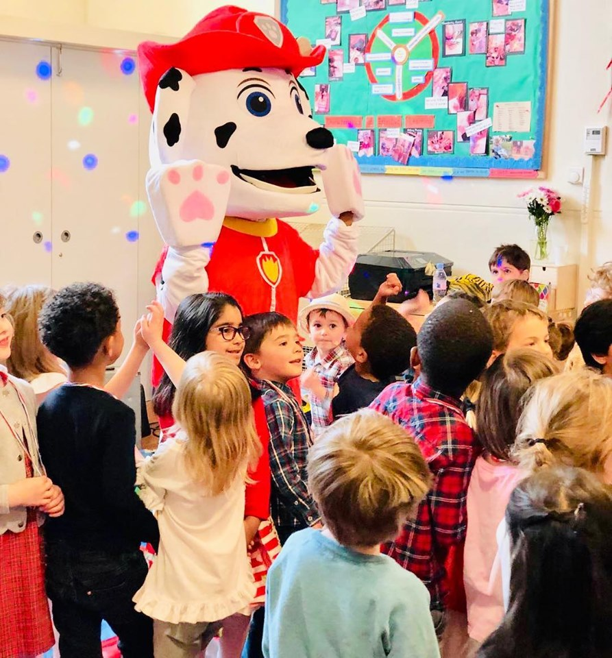 Paw patrol themed party. Kids giving mascot a high five