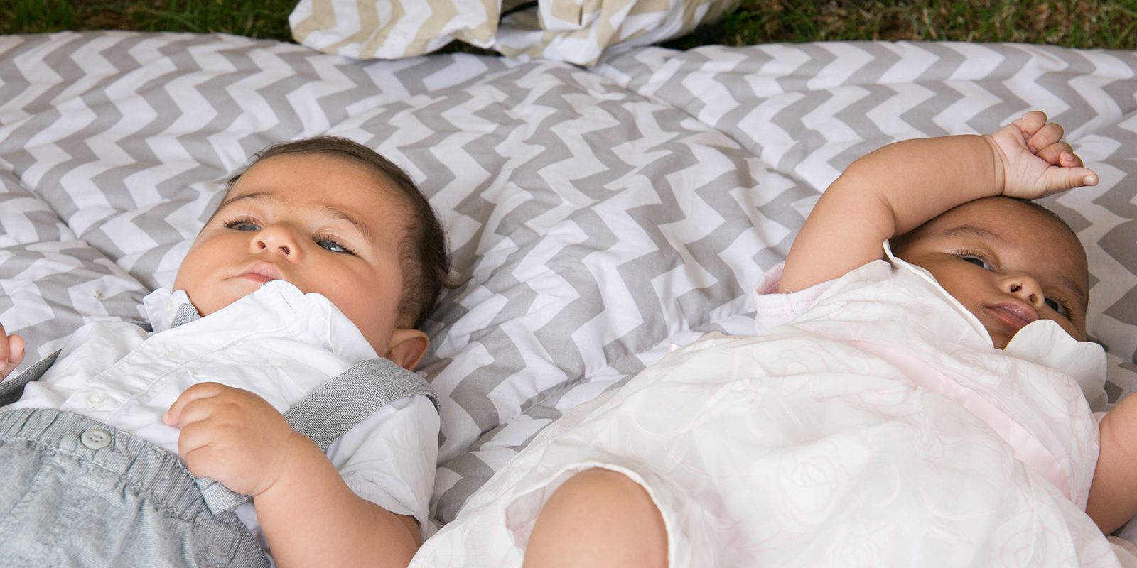 Two babies lying on the grass