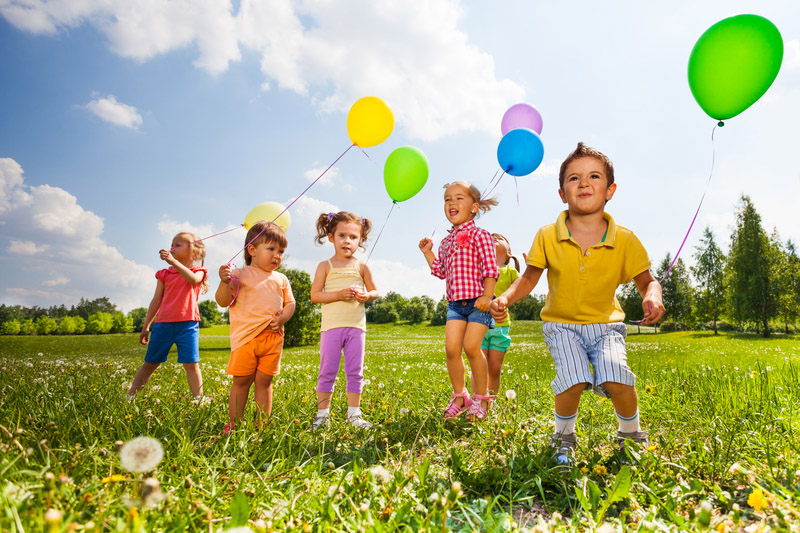 Children with colourful balloons running in field in summer